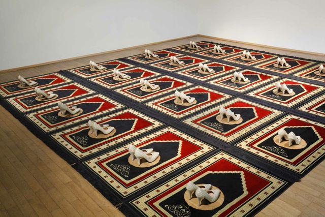Zoulikha Bouabdellah, Silence, 2008-2014, Installation: 24 prayer rugs, 24 pair of shoes 300 x 560 cm. Courtesy: the artist © Zoulikha Bouabdellah